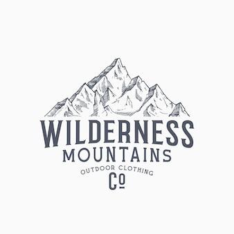 Wilderness mountains abbigliamento all'aperto vintage vector segno, etichetta o modello di logo. schizzo di picco di montagna disegnato a mano con tipografia retrò. emblema del marchio premium. isolato.
