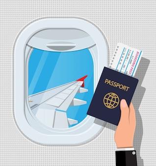 Finestra dall'interno dell'aereo. mano con passaporto e biglietto. otturatore e ala dell'oblò degli aerei. viaggio in aereo o concetto di vacanza. illustrazione in stile piatto