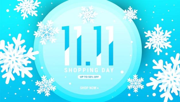 Banner di vendita 11.11 inverno con fiocchi di neve bianchi in una cornice di cerchio blu con posto per il testo.