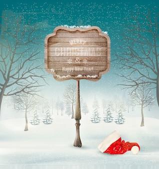 Paesaggio invernale di natale con un cartello ornato in legno e uno sfondo di cappello da babbo natale.