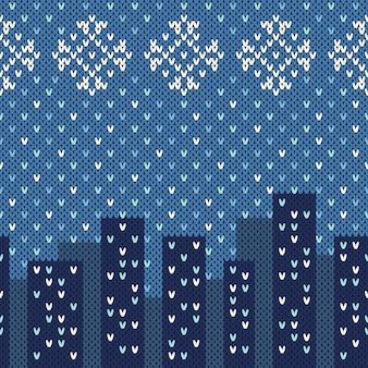 Modello senza cuciture orizzontale di inverno. vista della città sulla trama a maglia di lana.