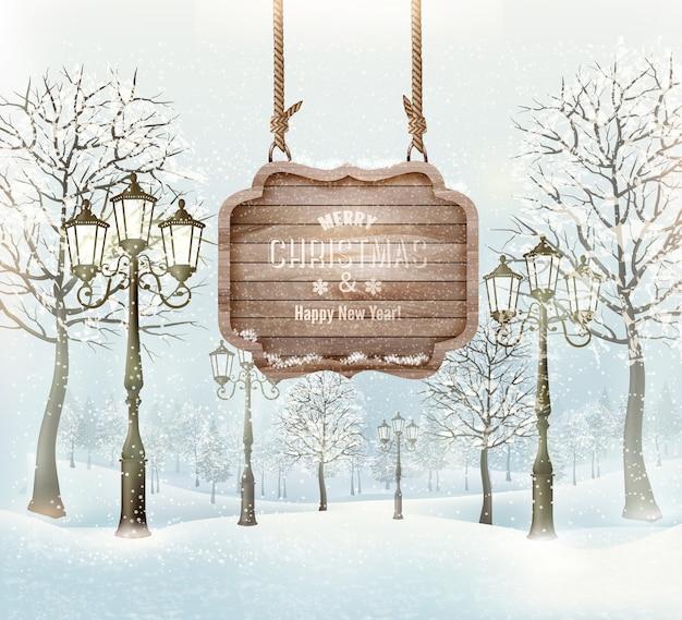 Paesaggio invernale con lampioni e un cartello di buon natale decorato in legno.