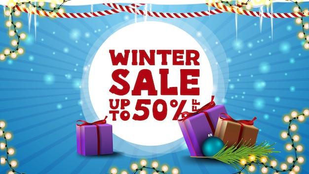 Saldi invernali, sconti fino a 50, banner sconto blu per sito web con ghirlande, ghiaccioli e regali