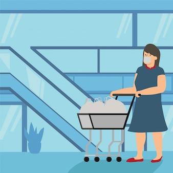 Una donna che porta il suo carrello in carrello al centro commerciale
