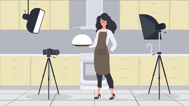 La cuoca in cucina conduce un vlog culinario. una ragazza con un grembiule da cucina tiene in mano un vassoio di metallo con un coperchio rotondo. vettore.