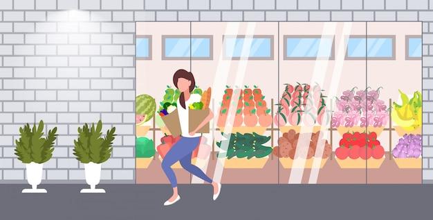 Cliente della donna che giudica i sacchi di carta in pieno dell'orizzontale integrale esteriore esterno del supermercato moderno moderno del negozio di alimentari di concetto di acquisto dei prodotti di drogheria delle drogherie