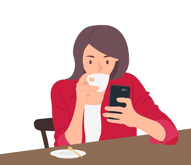 Donna che beve caffè e utilizzando il telefono cellulare seduto su una sedia