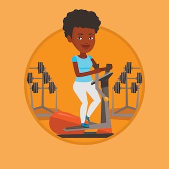 Donna che si esercita sull'addestratore ellittico.