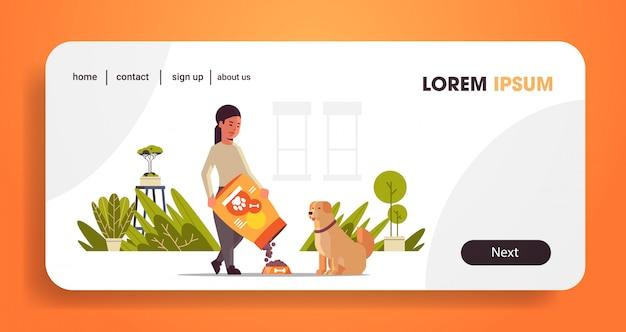 Donna che alimenta la ragazza affamata di labrador retriever che dà al suo cane vita domestica dei granelli asciutti dell'alimento con orizzontale integrale di concetto dell'animale domestico