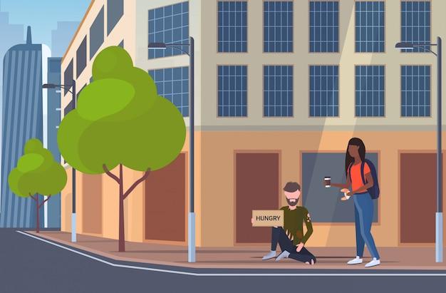 Donna che dà da mangiare al mendicante affamato uomo seduto sulla strada della città con cartello chiedendo aiuto senzatetto concetto di disoccupazione edificio esterno paesaggio urbano sfondo orizzontale a figura intera