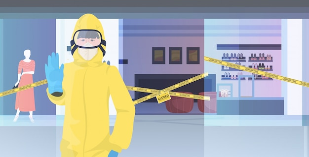 Donna in tuta hazmat mostrando fermata gesto centro commerciale con nastro giallo quarantena pandemia coronavirus