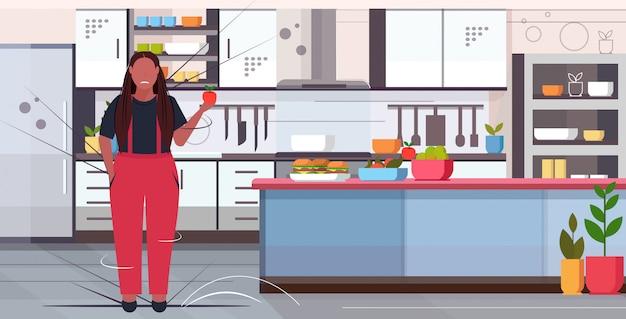 Donna con mela sovrappeso ragazza scelta tra frutta fresca e hamburger cibo spazzatura malsana perdita di peso dieta concetto interno cucina lunghezza integrale