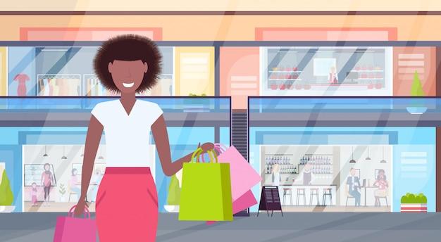 Donna che tiene il grande centro commerciale moderno di camminata di camminata della ragazza di concetto di vendita dei sacchetti della spesa variopinti con il ritratto orizzontale interno del supermercato delle caffetterie e dei vestiti piano