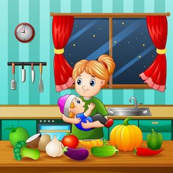 Una donna che tiene il suo bambino in cucina