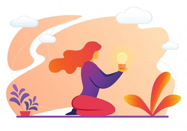 Donna che tiene la lampadina illuminata nelle mani.