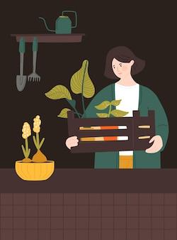 Donna che tiene una scatola di legno con piante d'appartamento giardiniere domestico che si prende cura delle piante in vaso