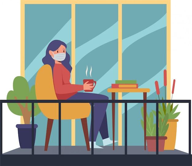 La donna si rilassa sul suo balcone di casa sorseggiando una tazza di tè caldo