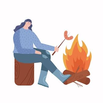 Una donna sta riposando all'aria aperta. donna che frigge la salsiccia al rogo.