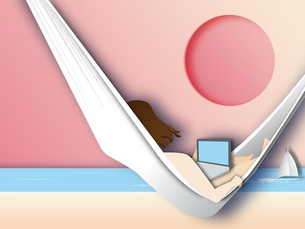 Donna che giace in un'amaca sulla spiaggia e usa il portatile.