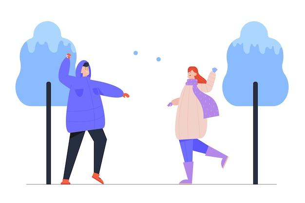 Donna e uomo che giocano a palle di neve sulla strada