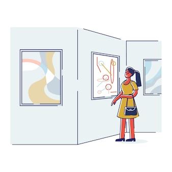 Donna nella galleria di arte moderna godere dell'esposizione dell'immagine donna del fumetto che guarda l'installazione di opere d'arte