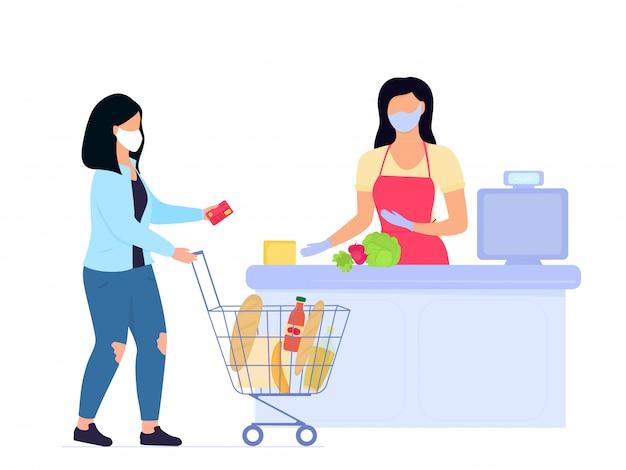 La donna nella mascherina medica protettiva con il carrello della spesa paga con la carta di credito alla cassa in supermercato. quarantena dell'epidemia di coronavirus covid-19