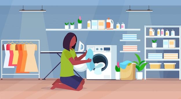Donna che mette i vestiti sporchi nella lavatrice casalinga afroamericana che fa lavoro orizzontale moderno interno completo del personaggio dei cartoni animati della lavanderia della casa di lavoro domestico