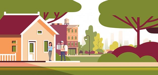 La donna riceve l'ordine dal corriere uomo in berretto con zaino e pacchetto di carta espresso consegna del cibo dal negozio o ristorante concetto moderno edificio casa esterno piatto orizzontale a figura intera