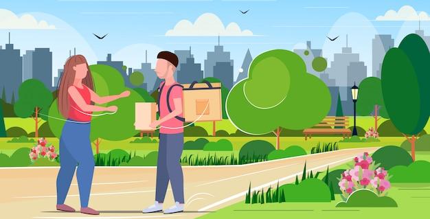La donna che riceve l'ordine dal corriere dell'uomo con il pacchetto dello zaino e della carta esprime la consegna dell'alimento dalla lunghezza orizzontale orizzontale del fondo di paesaggio urbano del parco di concetto del ristorante o del negozio