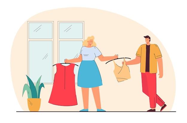 Donna che mostra nuovi vestiti all'uomo. moglie che mostra il nuovo top e il vestito al marito