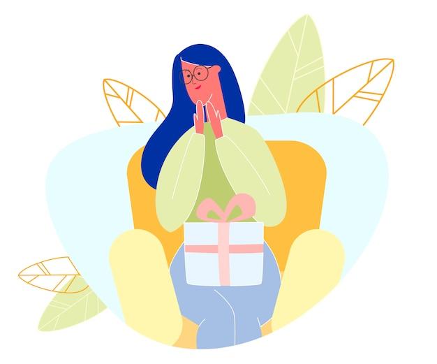 La donna si siede sulla poltrona che tiene il grande contenitore di regalo avvolto