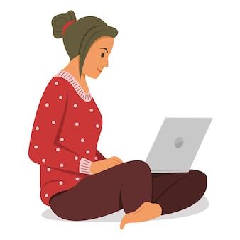 La donna si siede e lavora con il computer portatile.