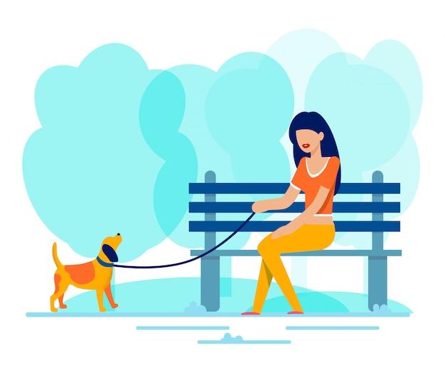 La donna si siede sul banco lungo cane a piedi nel parco