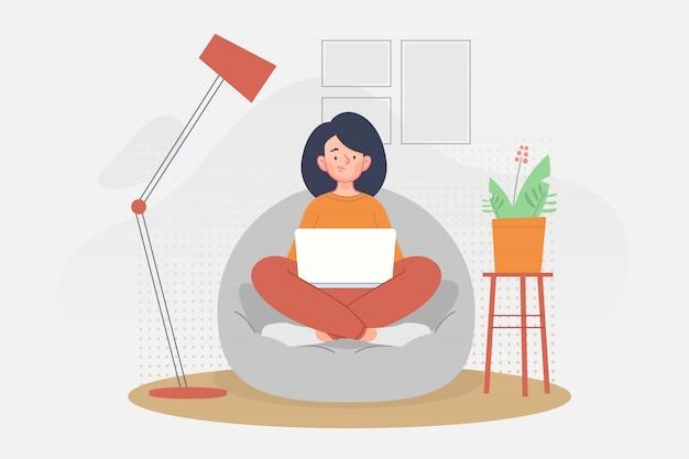 Donna che si siede sul sofà e che lavora con il computer portatile