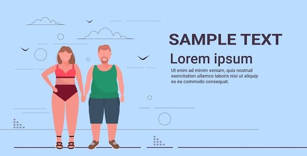 Donna in costume da bagno che si tiene per mano con l'uomo più le dimensioni coppia in piedi insieme orizzontale malsano concetto di obesità stile di vita malsano