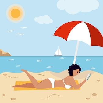 Una donna in costume da bagno si trova sulla spiaggia e legge un libro. turismo e viaggi. vacanza al mare.