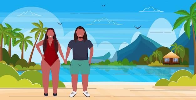 Donna in costume da bagno con uomo più dimensioni coppia in piedi insieme concetto di vacanze estive isola tropicale sfondo marino piena lunghezza orizzontale