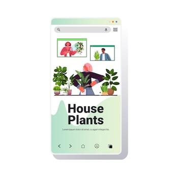 Donna che si prende cura delle piante d'appartamento casalinga discutendo con mix gara amici nelle finestre del browser web durante la videochiamata sullo schermo dello smartphone ritratto spazio copia