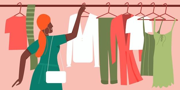 Donna che prova a scegliere i vestiti dell'attrezzatura di modo nella boutique o nello shopping dei consumatori