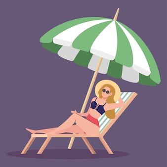 Donna che usando cappello estate con costume da bagno in spiaggia sedia, protezione dell'ombrello, stagione delle vacanze estive