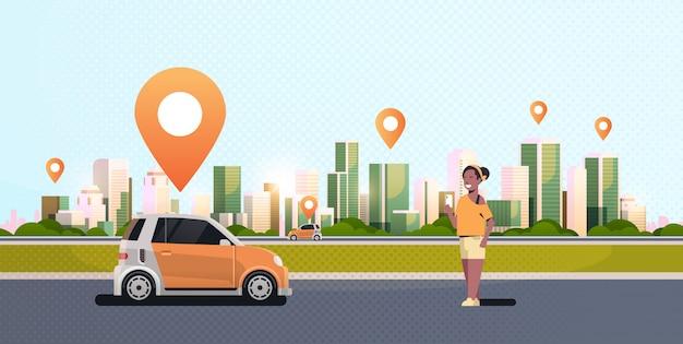 Donna che usando il veicolo di automobile d'ordinazione mobile di app con orizzontale moderno del fondo di paesaggio urbano di servizio di car sharing di concetto di car sharing di trasporto del segno di posizione