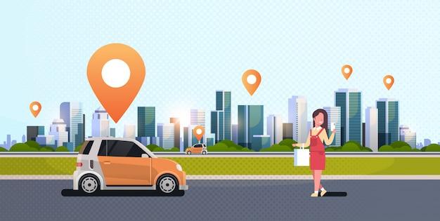 Donna che per mezzo di un'app mobile che ordina il veicolo automobilistico con il concetto di car sharing in affitto concetto di car sharing trasporto moderno paesaggio urbano