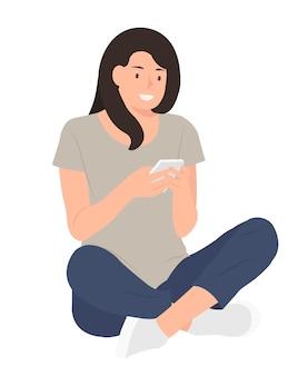 Donna che utilizza il telefono cellulare mentre era seduto su un pavimento con lascia incrociati