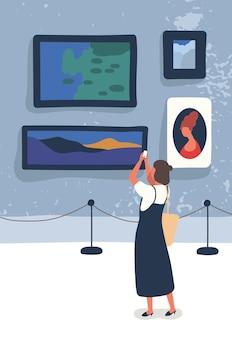 Illustrazione piana della galleria di visita della donna. giovane amante dell'arte che fotografa i personaggi dei cartoni animati