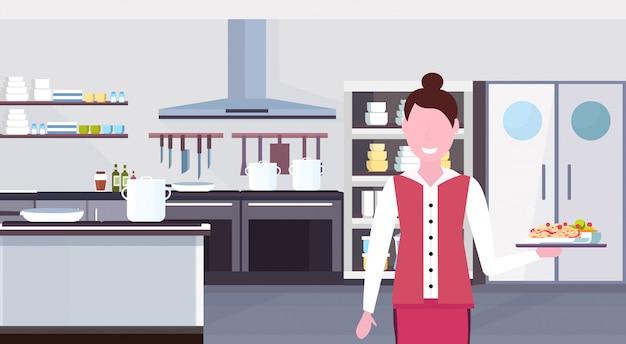 Vassoio della tenuta della cameriera di bar della donna con il lavoratore femminile del ristorante del pasto degli spaghetti in uniforme al ritratto orizzontale interno moderno della cucina commerciale piana