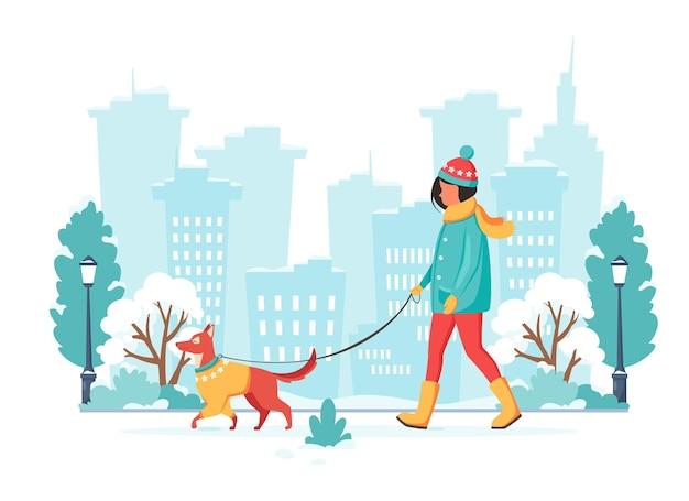 Donna che cammina con il cane nella città invernale