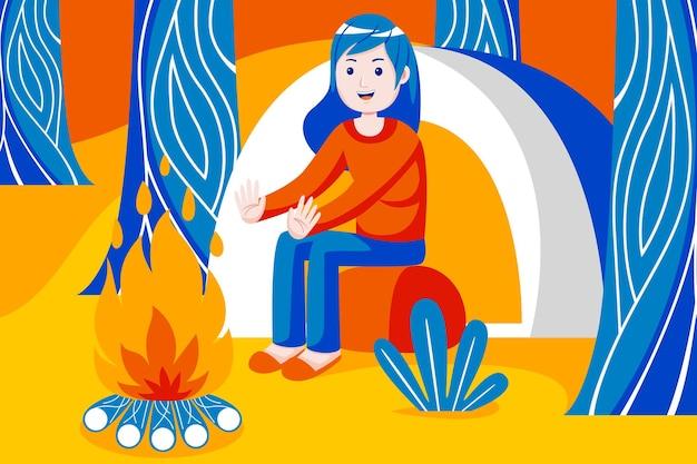 Donna calda vicino al fuoco nella foresta.