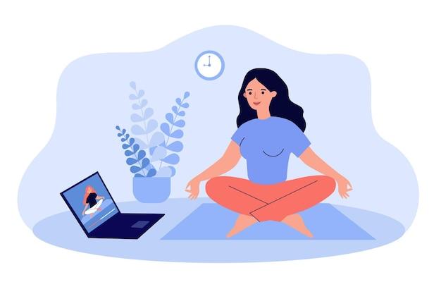 Donna che guarda la lezione di yoga video online sul computer portatile e facendo esercizi a casa