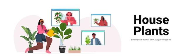 Donna che innaffia le piante d'appartamento casalinga afroamericana che discute con gli amici nelle finestre del browser web durante la videochiamata copia spazio
