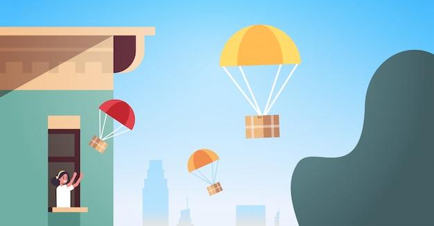Donna nella finestra che cattura la cassetta dei pacchi che cade con il paracadute dal cielo trasporto pacchetto di spedizione posta aerea concetto di consegna espresso moderno edificio esterno ritratto orizzontale